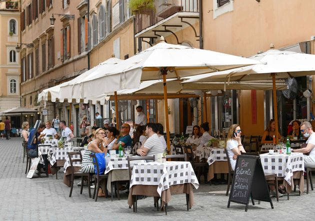 People sit on the terrace of a restaurant in Rome, Italy, on June 24, 2021. As of next week, Italy is...