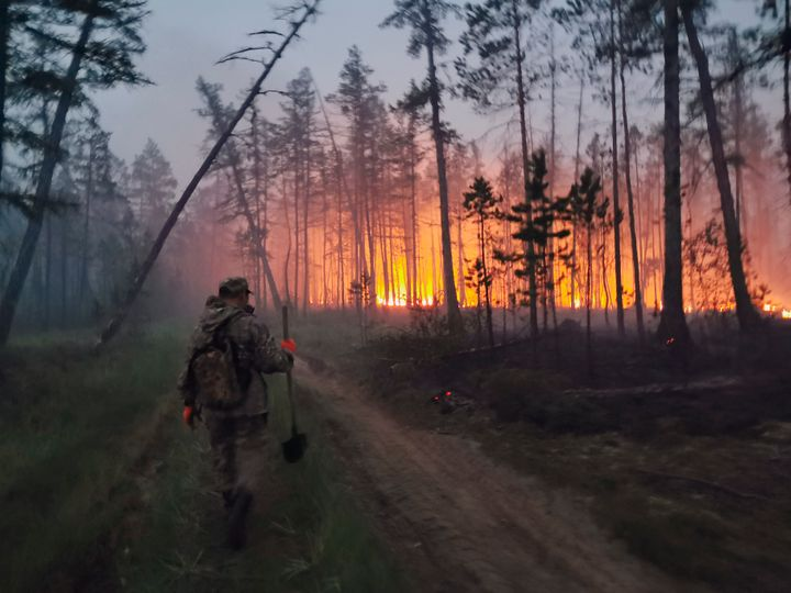In this Saturday, July 17, 2021 photo, a volunteer walks to douse a forest fire in the republic of Sakha also known as Yakuti