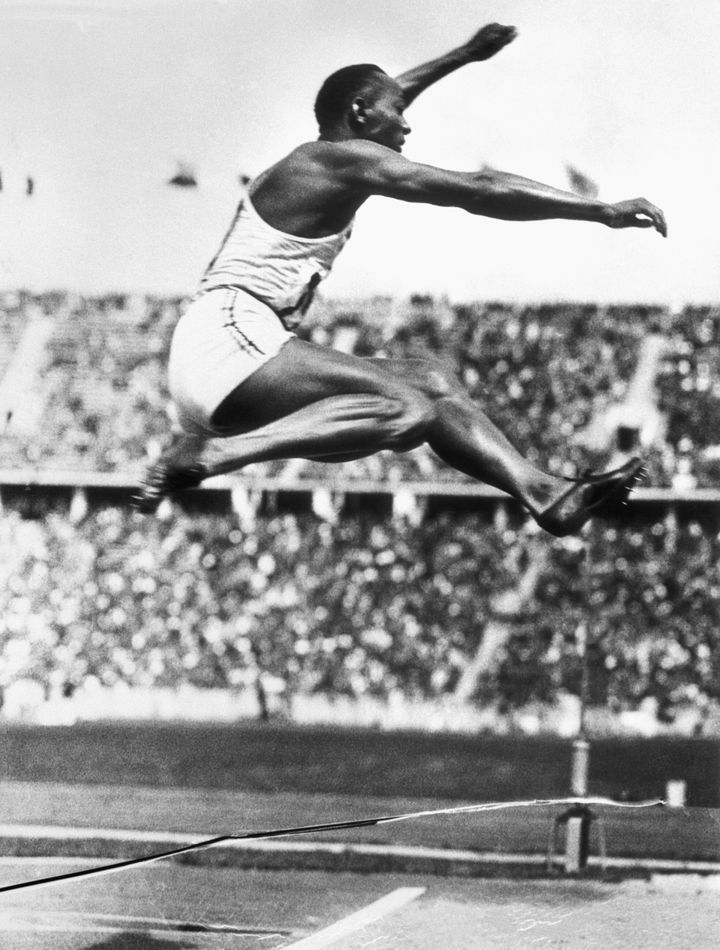 U.S. track star Jesse Owens makes the long jump that set an Olympic record in Berlin at the 1936 Olympic Games. His four gold
