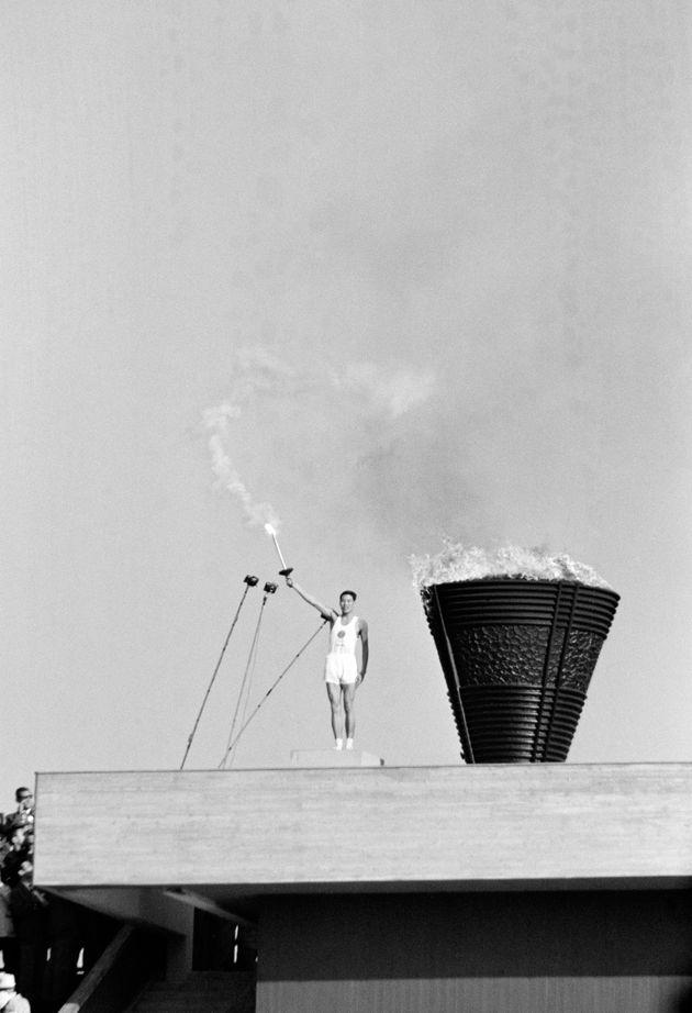 東京五輪の開会式で、聖火台に点火し、トーチを高々と掲げる最終走者の坂井義則(東京・国立競技場)