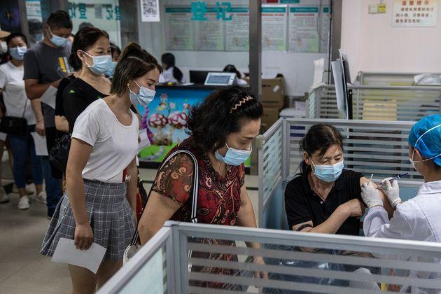 Personal sanitario chino vacunando a un grupo de personas en