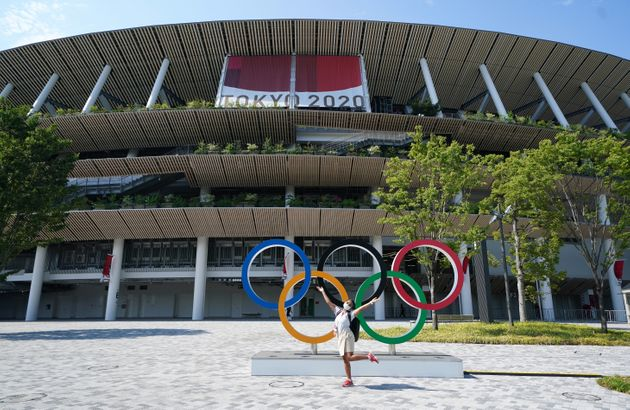 A person poses by the Olympic rings outside the stadium ahead of the opening ceremony of the Tokyo 2020...