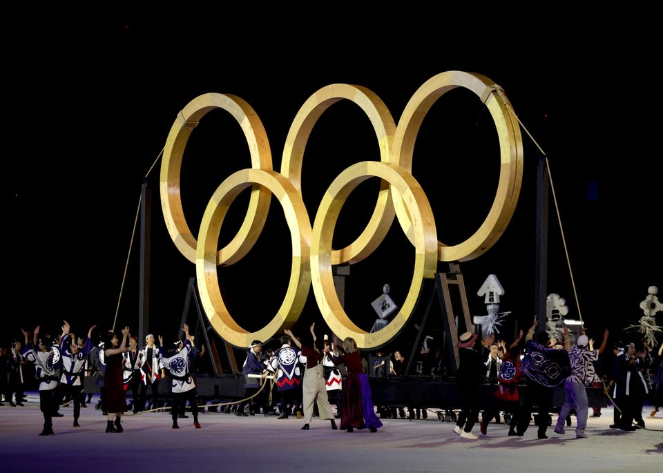 Performers dance in front of giant golden Olympic