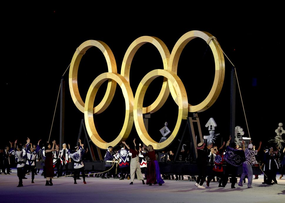 Performers dance in front of giant golden Olympic Rings.
