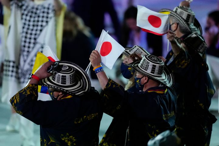 Colombian athletes wave Japanese flags as they enter the stadium.