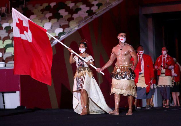TOKYO, JAPAN - JULY 23: Flag bearers Malia Paseka and Pita Taufatofua of Team Tonga lead their team out...