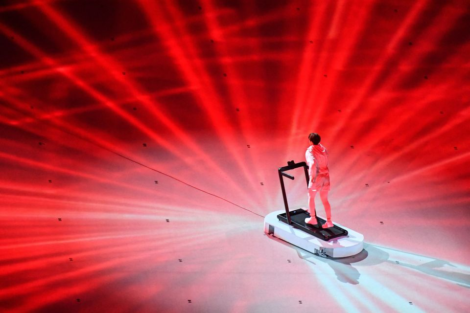 An overview shows a performer walking on a treadmill during the opening