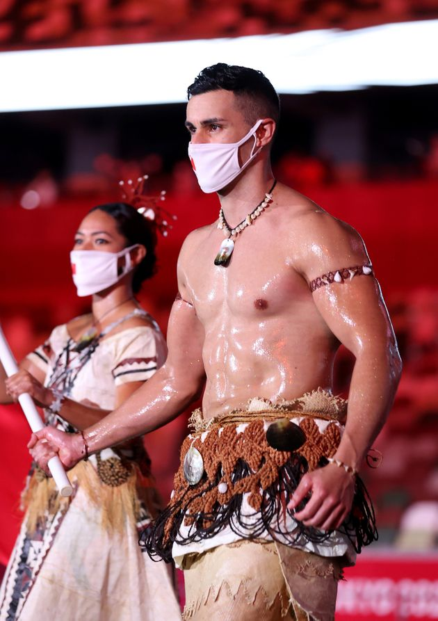 TOKYO, JAPAN - JULY 23: Flag bearer Pita Taufatofua of Team Tonga leads their team out during the Opening...