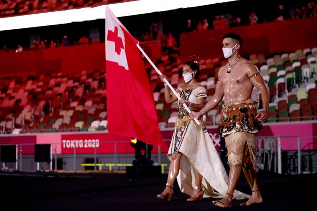 TOKYO, JAPAN - JULY 23: Flag bearers Malia Paseka and Pita Taufatofua of Team Tonga lead their team during the Opening Ceremony of the Tokyo 2020 Olympic Games at Olympic Stadium on July 23, 2021 in Tokyo, Japan. (Photo by Hannah McKay - Pool/Getty Images)