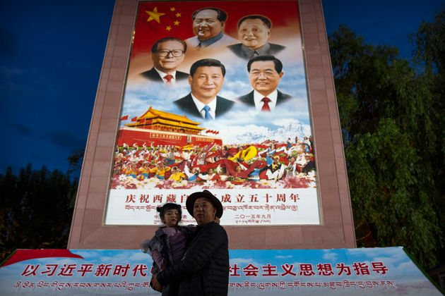 A man holds a girl as they pose for a photo in front of a large mural depicting Chinese President Xi...