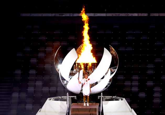 TOKYO, JAPAN - JULY 23: Naomi Osaka of Team Japan lights the Olympic cauldron with the Olympic torch...