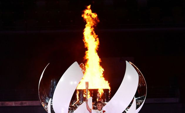 Japanese tennis player Naomi Osaka holds the Olympic Torch after lighting the flame of hope in the Olympic Cauldron during the opening ceremony of the Tokyo 2020 Olympic Games, at the Olympic Stadium, in Tokyo, on July 23, 2021. (Photo by Franck FIFE / AFP) (Photo by FRANCK FIFE/AFP via Getty Images)