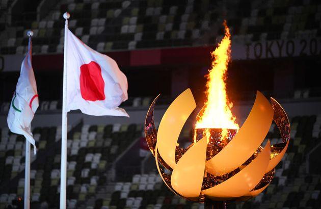 La llama olímpica arde junto a la bandera de Japón en los Juegos de Tokio