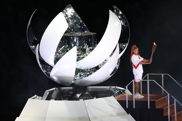 Tennis player Naomi Osaka lights the Olympic Cauldron atop a mini Mount Fuji at the opening ceremony of the Tokyo 2020 Summer
