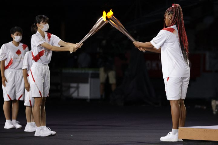 Japan's tennis player Naomi Osaka (R) lights her Olympic Torch before lighting the flame of hope in the Olympic Cauldron duri