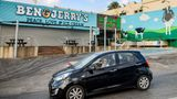 """A motorist drives past a closed """"Ben & Jerry's"""" ice-cream shop in the Israeli city of Yavne, about 30 kilometres south of Tel Aviv, on July 23, 2021. - On July 19, Vermont-based Ben & Jerry's announced it would no longer sell its ice cream in the Israeli-occupied Palestinian territories, namely the West Bank and East Jerusalem, which have been under control of the Jewish state since 1967. More than 670,000 Jewish settlers live in the two territories, in communities widely regarded as illegal under international law. (Photo by AHMAD GHARABLI / AFP) (Photo by AHMAD GHARABLI/AFP via Getty Images)"""