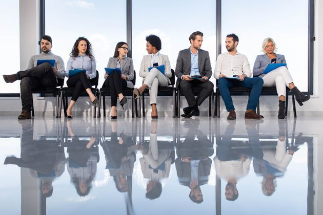 Large group of entrepreneurs sitting on chairs in waiting room before their job interview. Their reflection...