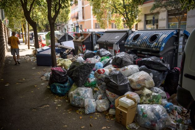 ROME, ITALY - JULY 07: A resident walks past overflowing trash bins on the streets, as the city struggles with a garbage problem aggravated by the summer heat, on July 7, 2021 in Rome, Italy. (Photo by Antonio Masiello/Getty Images)