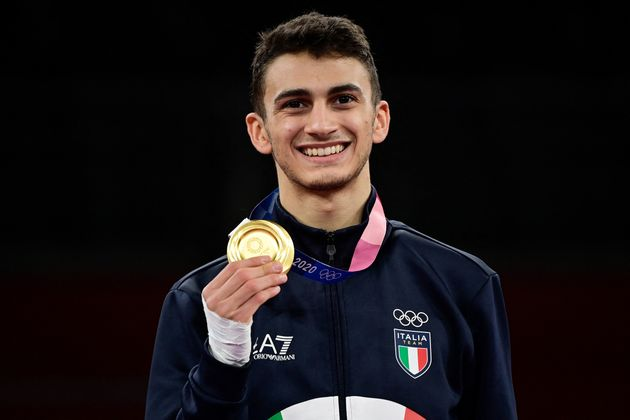 Italy's Vito Dell'aquila celebrates with his gold medal on the podium after winning the taekwondo men's...