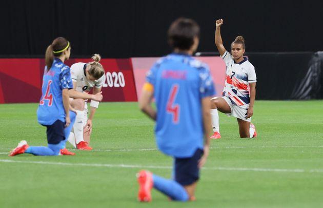試合前に片膝をついて人種差別への抗議を示す日英の選手=7月24日、札幌ドーム