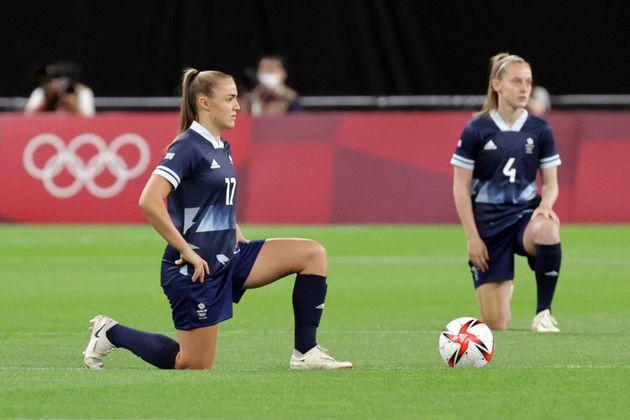 7月21日のサッカー女子予選リーグで、片膝をつくイギリス代表チーム。対戦するチリ代表チームも片膝をつき、連帯を示した。