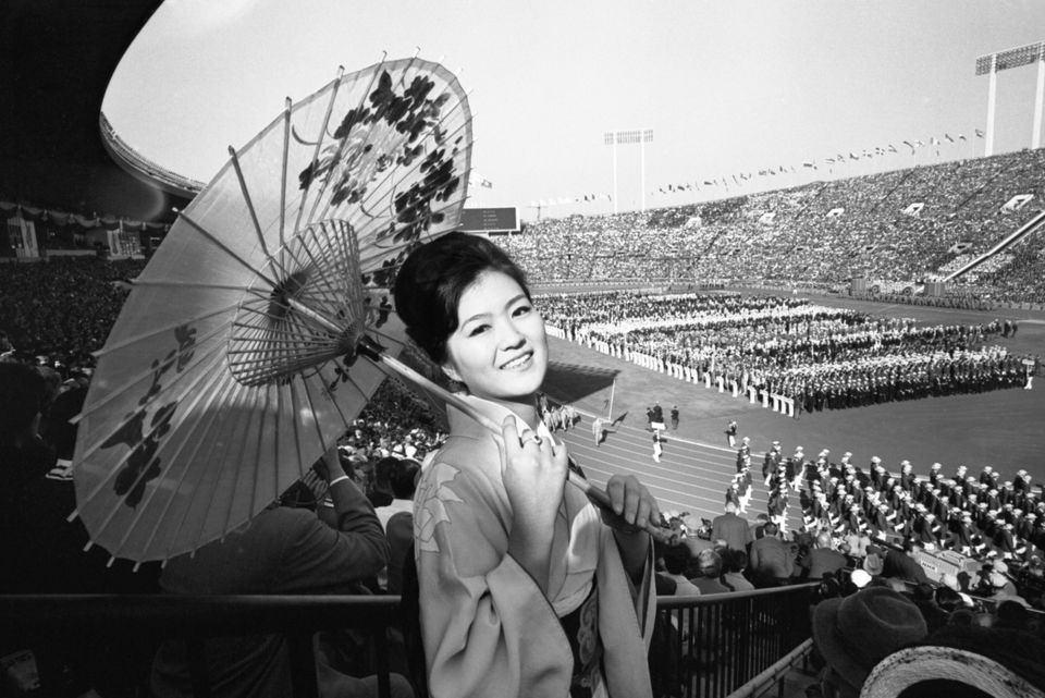 Traditionally garbed Yuko Shibayama of Tokyo watches the colorful opening ceremonies of the 18th Olympiad...