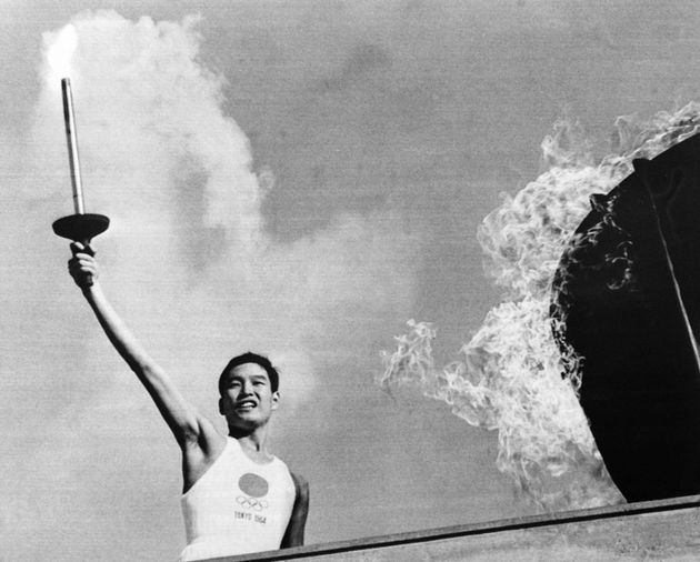 Picture taken on October 10, 1964 at Tokyo showing Japanese Olympic torch runner Yoshinori Sakai from Hiroshima after lighting the Olympic torch during the opening ceremony of the 1964 Tokyo Olympic Games. (Photo by - / AFP) (Photo by -/AFP via Getty Images)