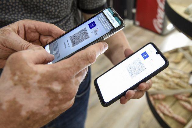 Des personnes utilisant une application de vérification de pass sanitaire sur des smartphones...