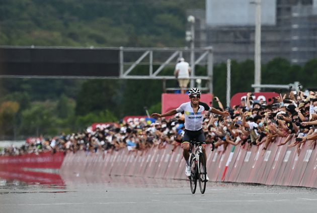 Ecuador's Richard Carapaz celebrates as he rides to the finish line to win the men's cycling road race...