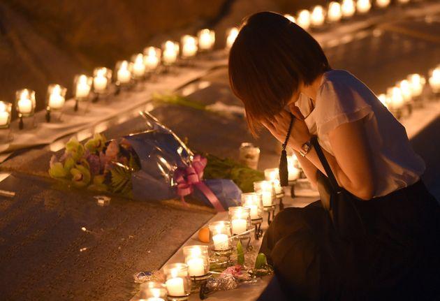 群馬県上野村で行われた追悼式典で手を合わせる女性=2015年8月12日撮影