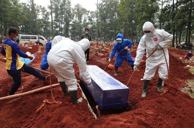 Eθελοντές θάβουν πτώμα νεκρού από κορονοϊό στη Δυτική Τζάβα της Ινδονησίας. (AP Photo/Achmad Ibrahim)