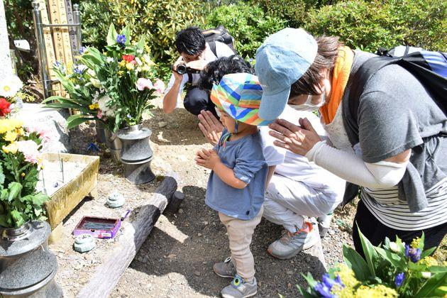 日航機墜落事故の現場に建つ「昇魂之碑」の前で手を合わせる遺族ら=2020年8月12日撮影
