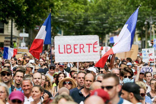 MARSEILLE, FRANCE - 2021/07/24 : Un activiste tient une pancarte pendant la manifestation contre le pass...