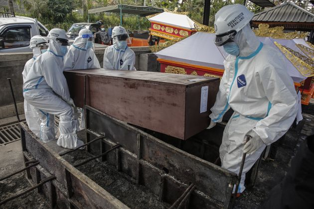 BALI, INDONESIA - JULY 25: Funeral workers wear personal protective equipment carry the coffin of Covid-19...