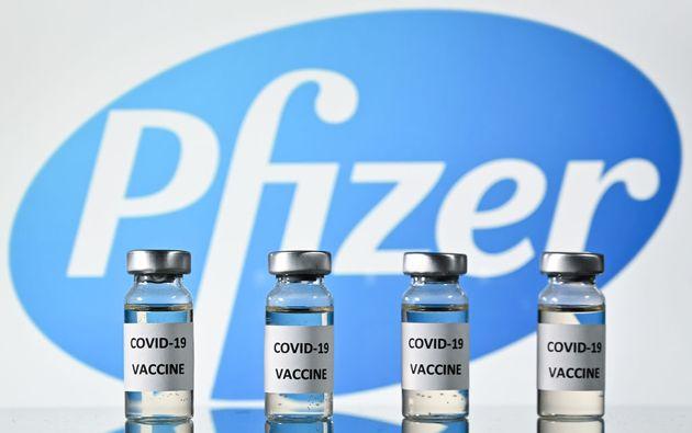 2020년 11월 17일 코로나19 백신 스티커가 부착된 병 뒤로 미국 제약회사 화이자(Pfizer)의 로고가