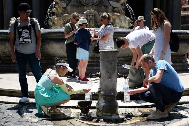 Tourists drink and fill their bottle from a public fountain to refresh themselves during an unusually...