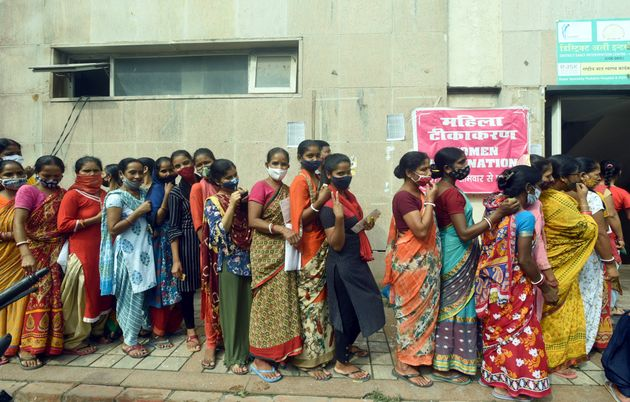NOIDA, INDIA - JULY 23: People flout social distancing norms as they wait to receive Covid-19 vaccine...