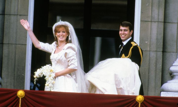 Sarah Ferguson and Prince Andrew stand on the balcony of Buckingham Palace and wave at their wedding on July 23, 1986, in Lon