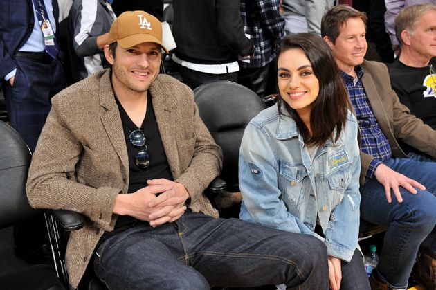 Ashton Kutcher and Mila Kunis at a basketball game in