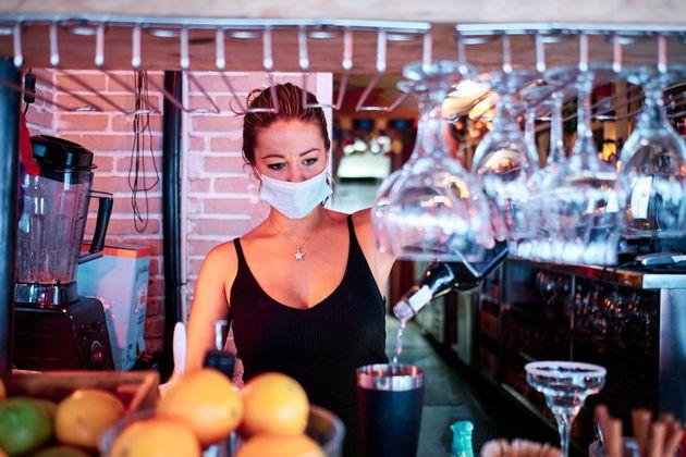 Una camarera prepara una bebida en el interior de un