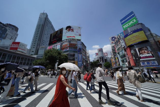 People wearing face masks to help curb the spread of the coronavirus walk across a busy crossing at Shibuya district in Tokyo Saturday, July 24, 2021, a day after the opening of the Tokyo Olympics. (AP Photo/Kantaro Komiya)