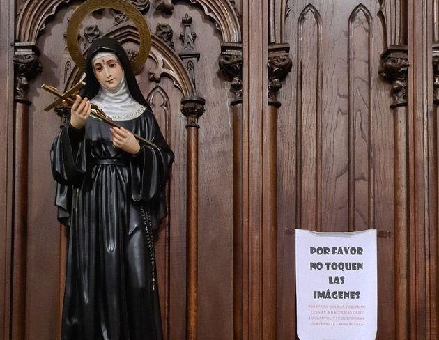 El cartel colgado junto a una virgen de la iglesia de Santiago, en