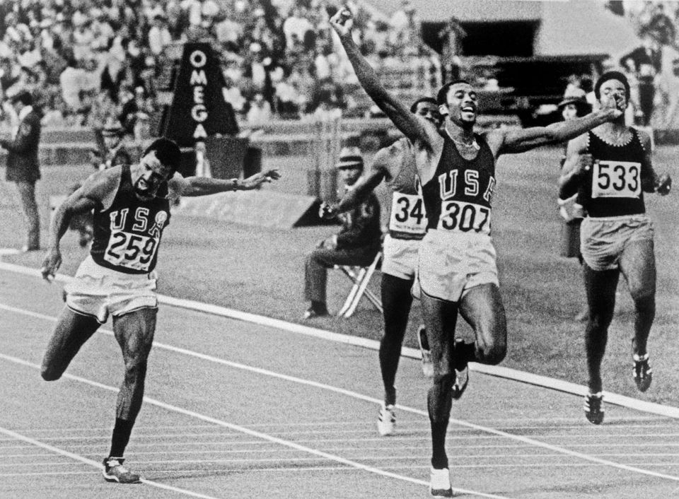 American athlete Tommie Smith (2nd R) jubilates after crossing the finish line of the men's 200m final...