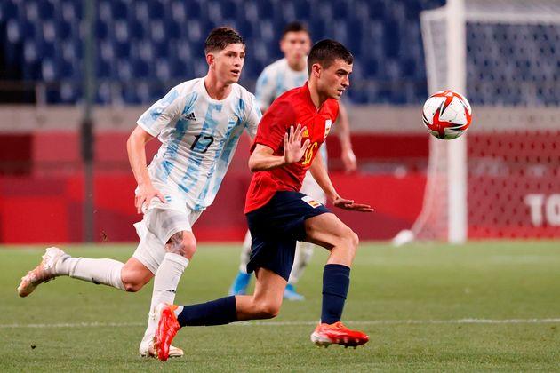El centrocampista español Pedri, disputando el balón al argentino Tomás