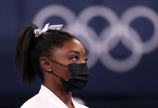 La gymnaste Simone Biles, de l'équipe des États-Unis, regarde son équipe aux barres asymétriques à la...