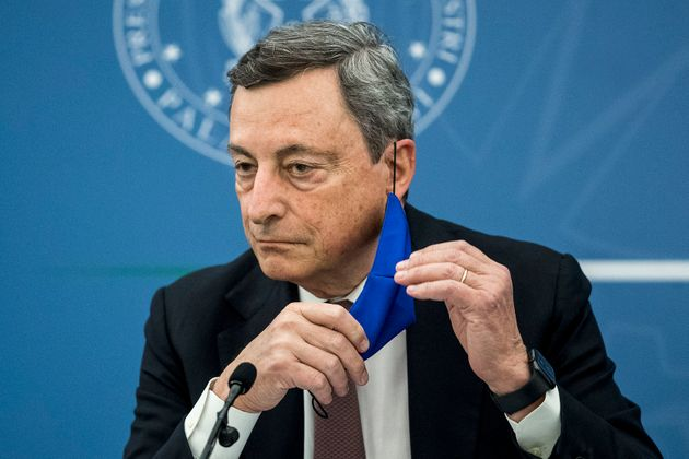 Italian Prime Minister Mario Draghi removes his face mask during a press conference with Italy's Justice...