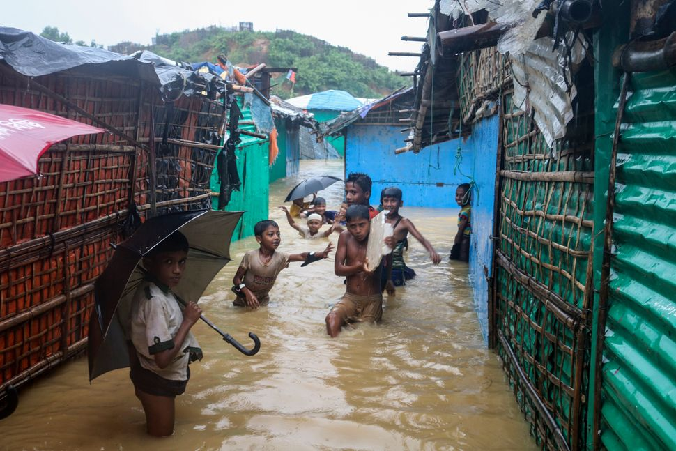 Rohingya refugee children play in floodwaters at the Rohingya refugee camp in Kutupalong, Bangladesh on Wednesday.