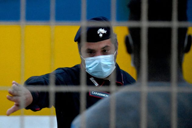 A security official watches migrants from a migrant housing centre on the Italian island of Lampedusa,...