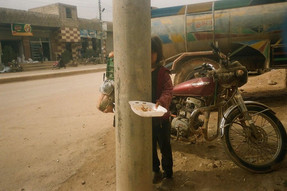 Questa bambina sta mangiando lo scarto di qualcun altro. Foto scattata da Yousef, 13