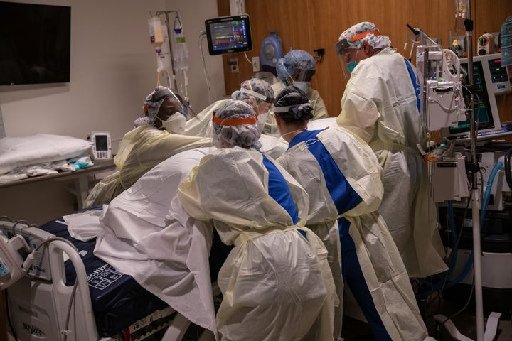"""A """"prone team,"""" wearing personal protective equipment (PPE), turns a COVID-19 patient onto his stomach in a Stamford Hospital"""